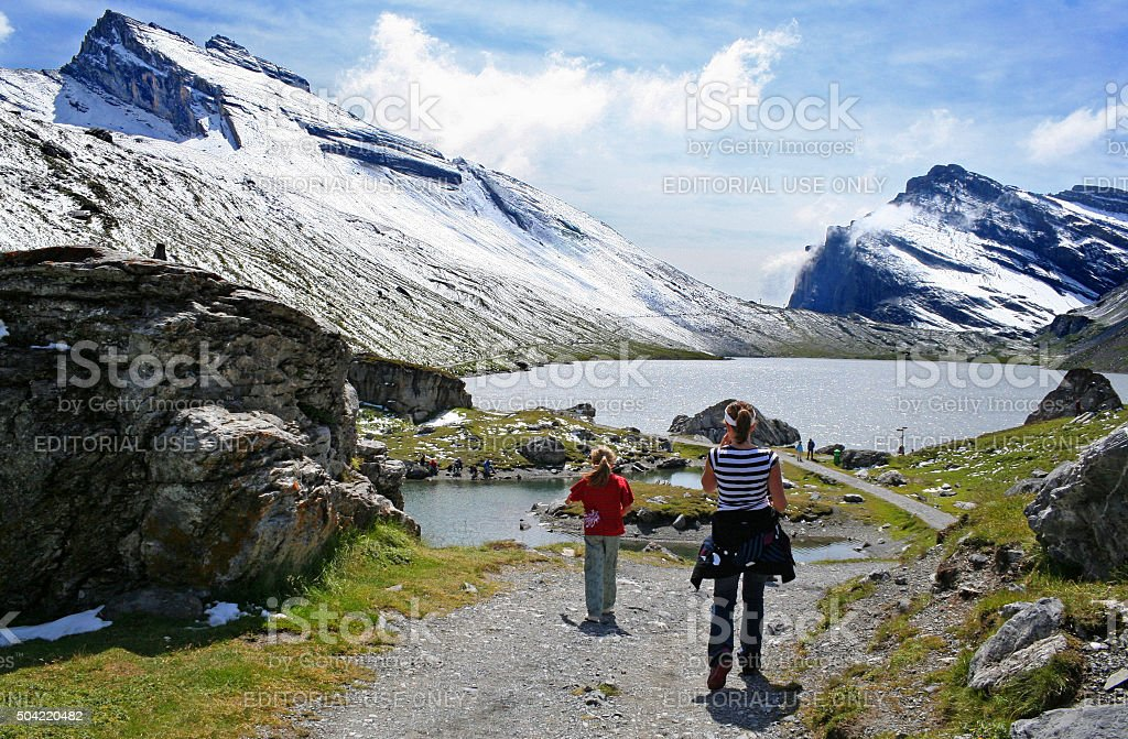 Hikers near Lake Daubensee and Gemmi pass with summer snow stock photo