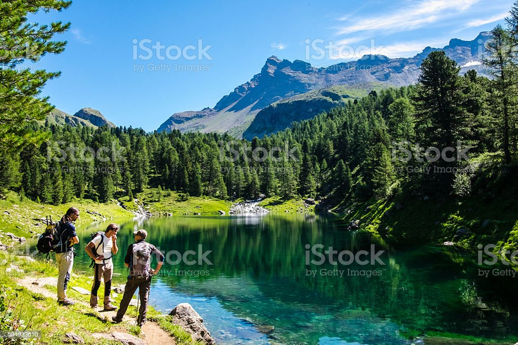 Hikers on a mountain path near alpine lake stock photo