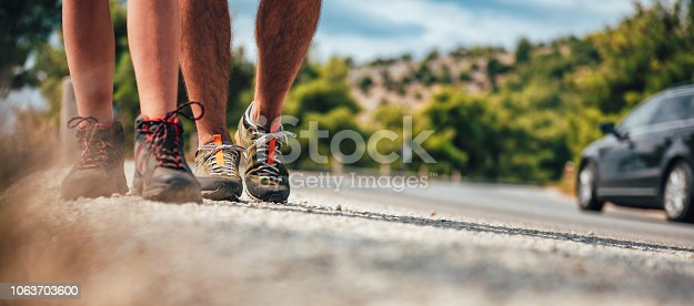istock Hikers on a mountain road passing by the car 1063703600