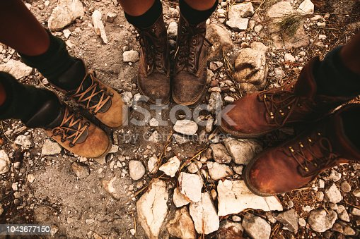 Closeup of hikers shoes on rocky trail. Man and women standing together on rocky path wearing trekking boots.