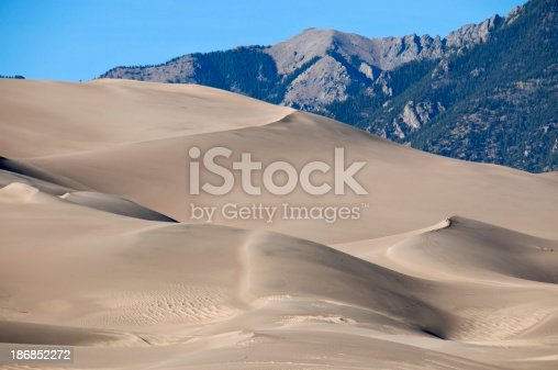 Hikers on sand dunes at foot of Rocky mountains in Colorado