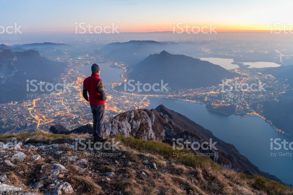 Hikers on the top of the mountain above the city stock photo