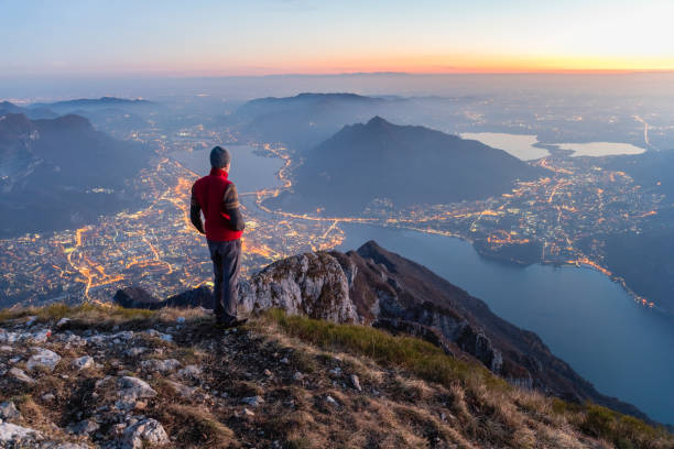 hikers on the top of the mountain above the city - distant stock photos and pictures