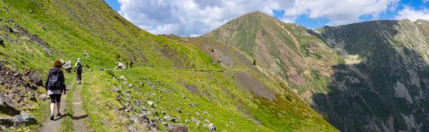 hikers passing on the road carrilet, aiguestortes national park - lleida стоковые фото и изображения