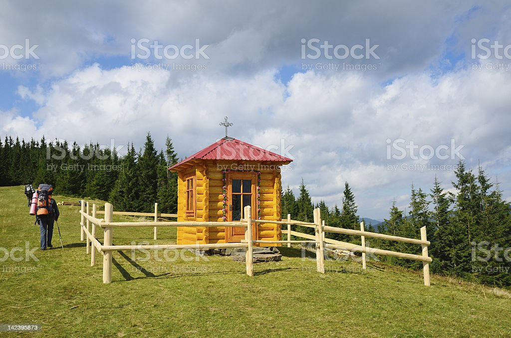 Hikers past the chapel in Carpathian Mountains. royalty-free stock photo