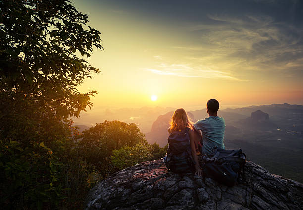 Hikers Two hikers on top of the mountain enjoying sunrise over the tropical valley explorer stock pictures, royalty-free photos & images
