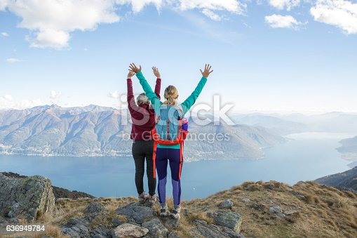 Couple of hikers reaching the mountain top celebrating. Arms outstretched for freedom and positive emotion.