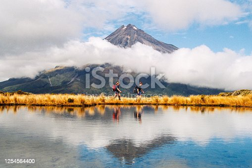 Hiker Heterosexual couple Reflection of Mount Taranaki Egmont in natural lake