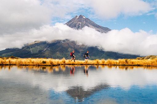 Hiker Heterosexual couple Reflection of Mount Taranaki Egmont in natural lake
