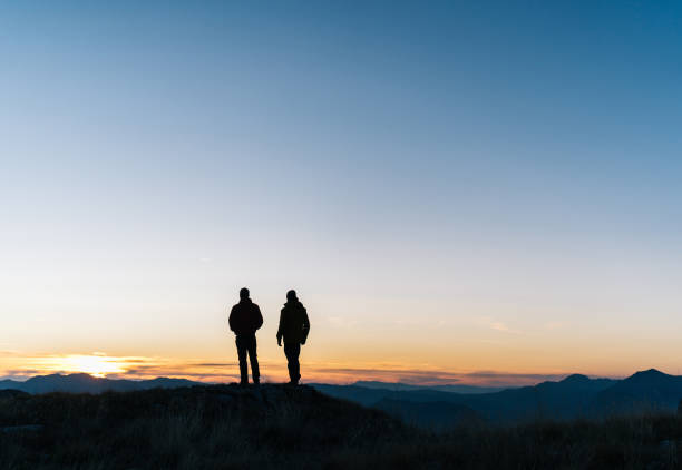 Hikers relaxes above mountain valley at sunrise stock photo