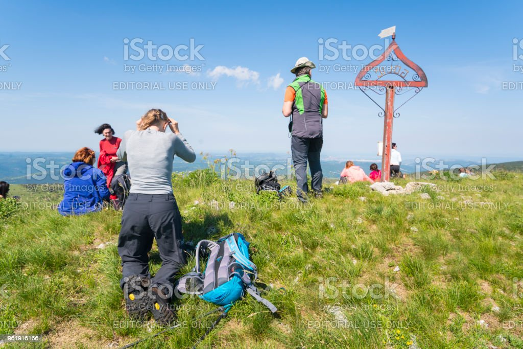 Hikers rest after long hiking on Golic, top of Zalipnik valley saddle, and looking towards Adriatic, Slovenian Istria near Croatia border royalty-free stock photo