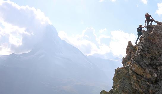 Hikers scramble up steep hillside near the Matterhorn peak