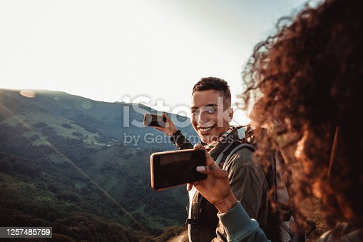 Close up of two hikers taking a photo of a sunset