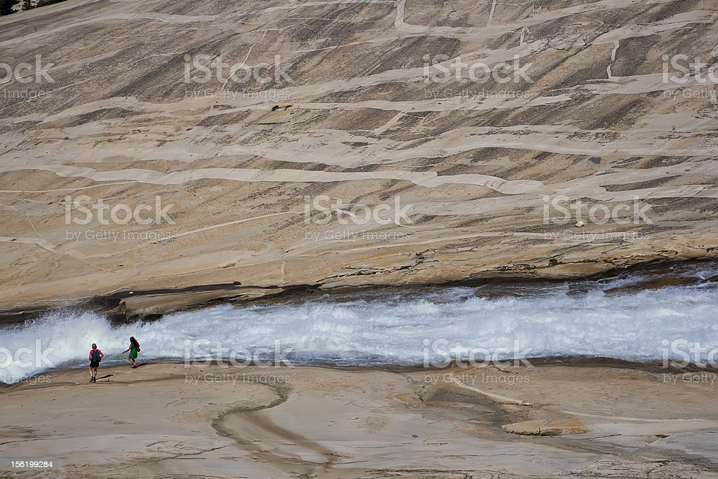 Hikers trekking along cascades. royalty-free stock photo