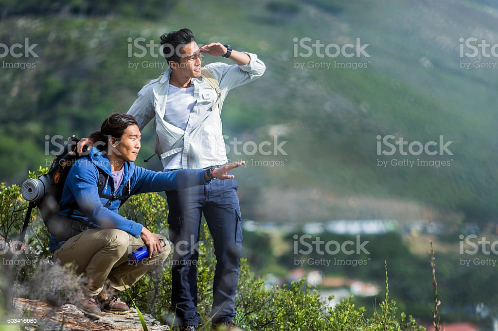 Hikers viewing the scenery while relaxing on hill stock photo