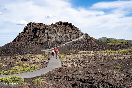 Arco, Idaho - June 30, 2019: Hikers walk up the Spatter Cones trail, a paved walkway leading to a cinder cone wi in Craters of the Moon National Monument in Idaho
