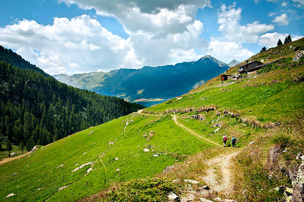 Hikers Walking on Mountain Footpath in Alps of Italy stock photo