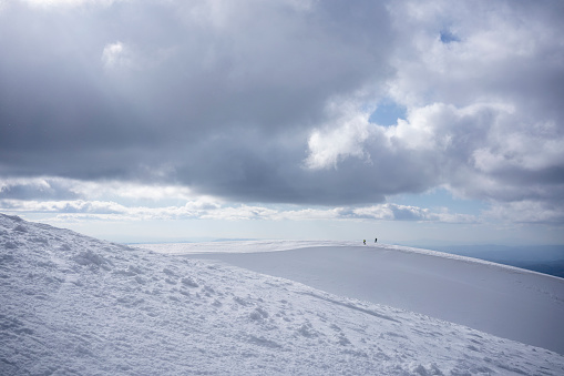 Hikers walking on the snowy plateau hill