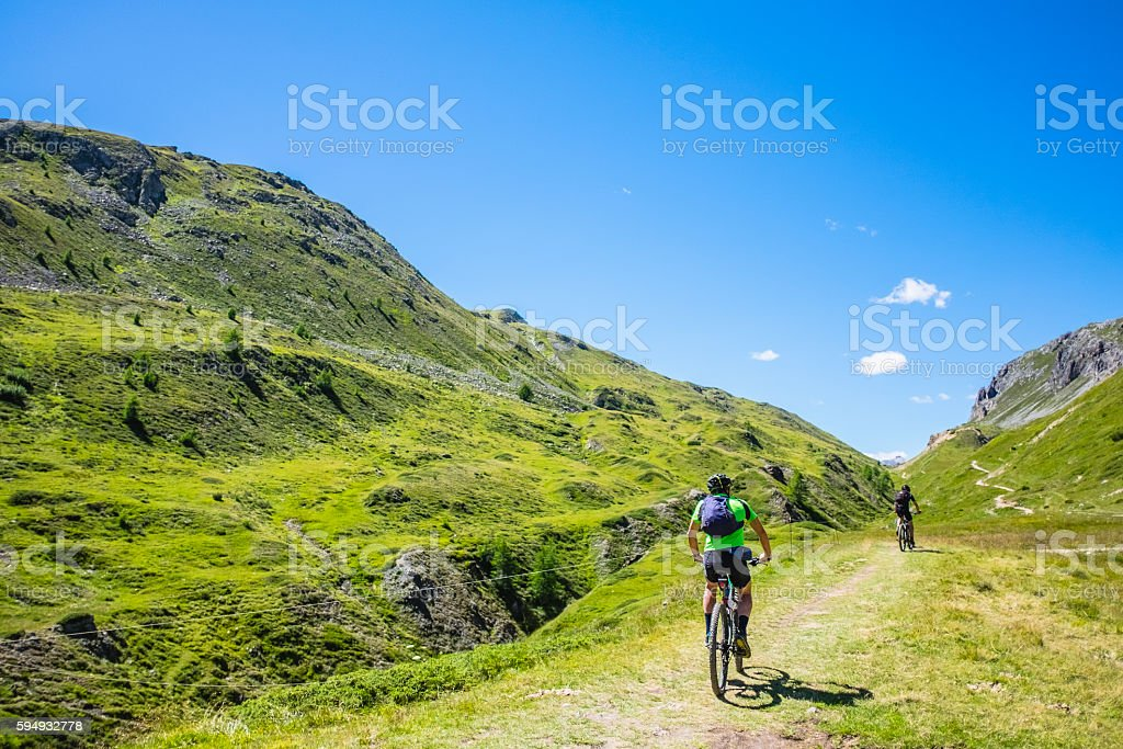 Hikers with mountain bike in a mountain valley stock photo