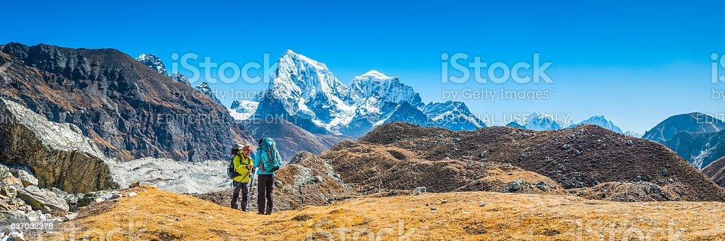 Hikers with rucksacks on mountain wilderness trail panorama Himalayas Nepal stock photo
