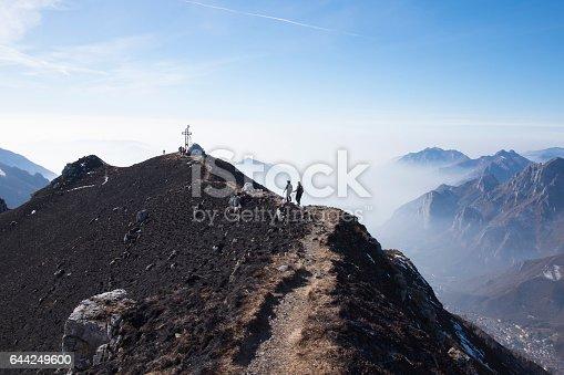 istock Hikers woman walking on a mountain ridge 644249600