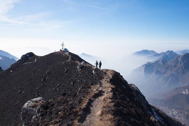 Hikers woman walking on a mountain ridge stock photo