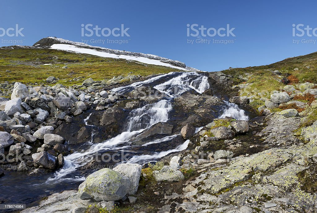 Hiking along small waterfall in autumn colored high mountains royalty-free stock photo