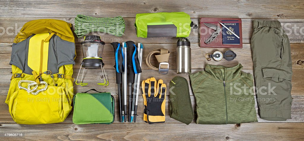 Hiking and camping gear organized on rustic wooden boards stock photo