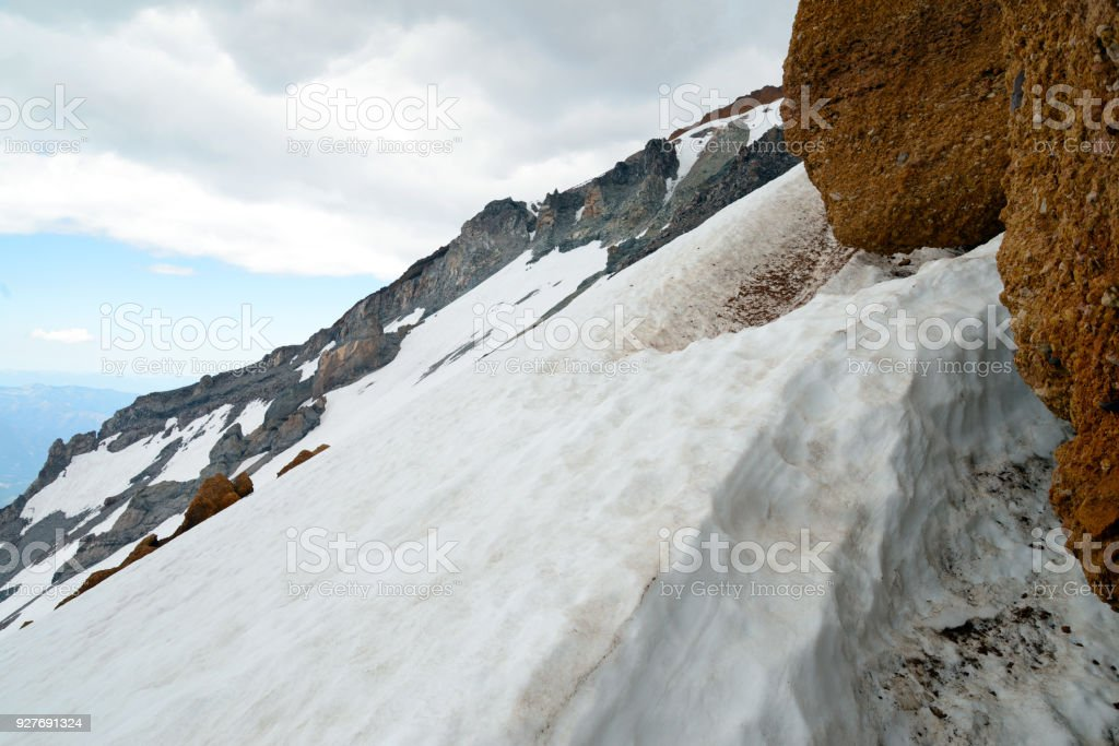 Hiking and climbing terrain on Mount Shasta volcano, California 14er in the Cascade Range where glaciers, avalanches and steep snow are risks climbers and mountaineers contend with some claim climate change is influencing. stock photo
