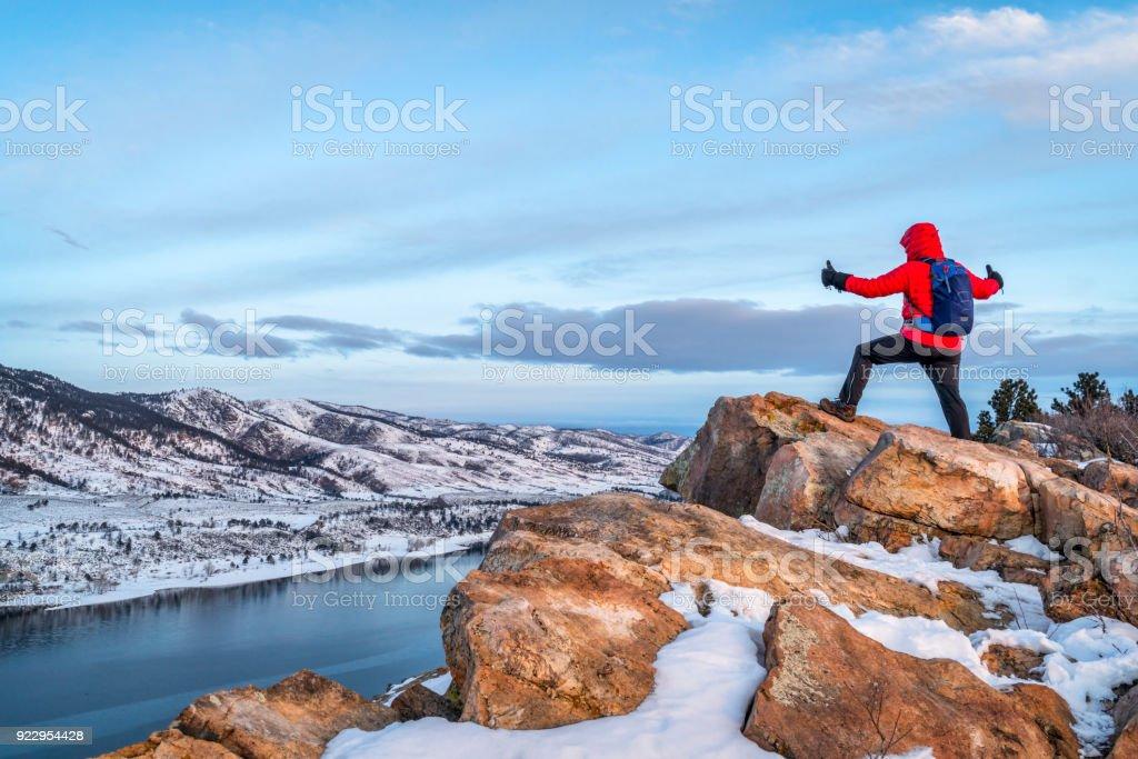 hiking at dawn over frozen mountain lake stock photo