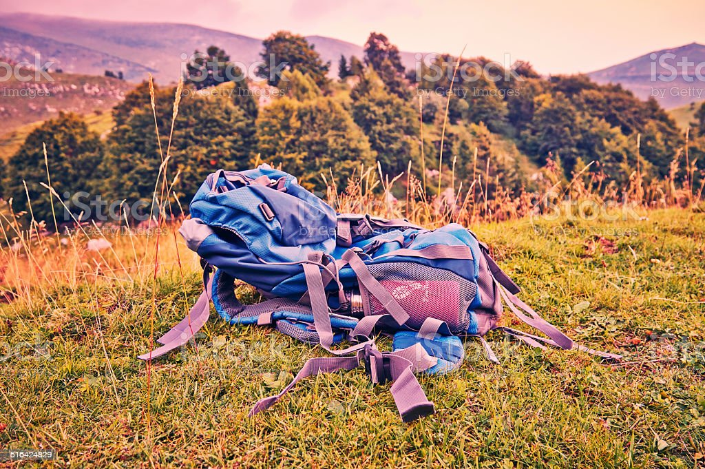 Hiking backpack lying in grass on mountain. stock photo