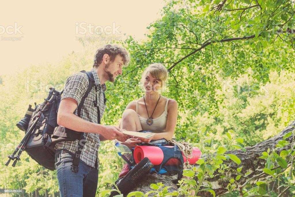 Hiking backpacking couple reading map on trip. zbiór zdjęć royalty-free
