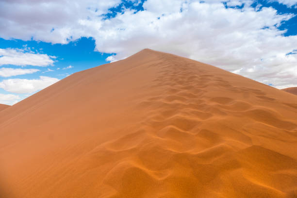 Hiking Big Daddy, among the world's tallest dunes near Sossusvlei in the Namib-Naukluft National Park of Namibia. Hiking Big Daddy, among the world's tallest dunes near Sossusvlei in the Namib-Naukluft National Park of Namibia. antipode stock pictures, royalty-free photos & images