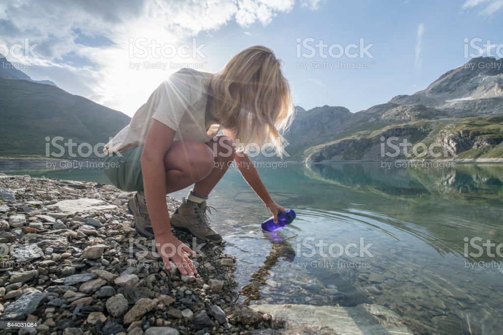 Hiking blond girl filling bottle from mountain lake stock photo