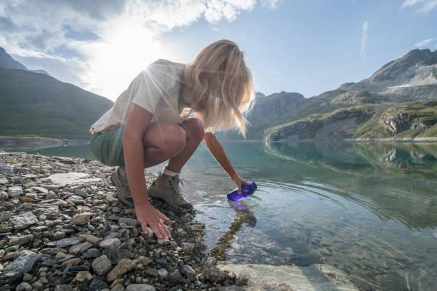 山の湖からブロンドの女の子充填ボトルをハイキング - 自然旅行 ストックフォトと画像