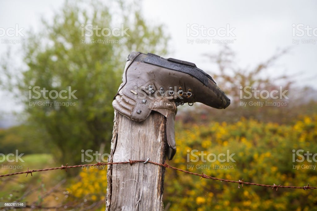 A hiking boot places upside down on a wooden pole somewhere along the Camino Santiago - foto stock