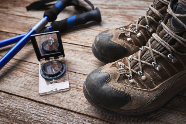 hiking boots and compass stock photo