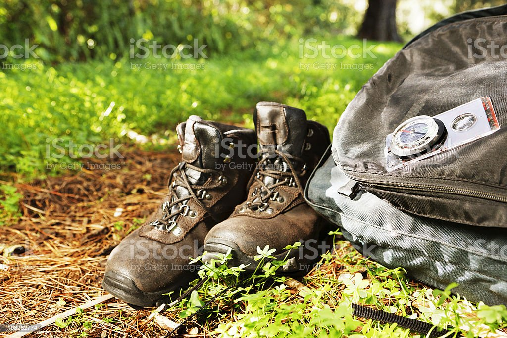 Hiking boots, backpack, compass, next to woodland path royalty-free stock photo