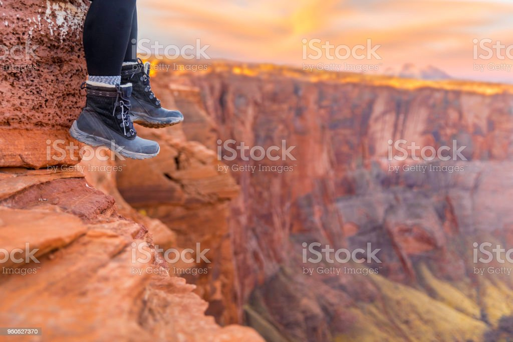 Hiking Boots Dangling over Cliff at Sunrise stock photo
