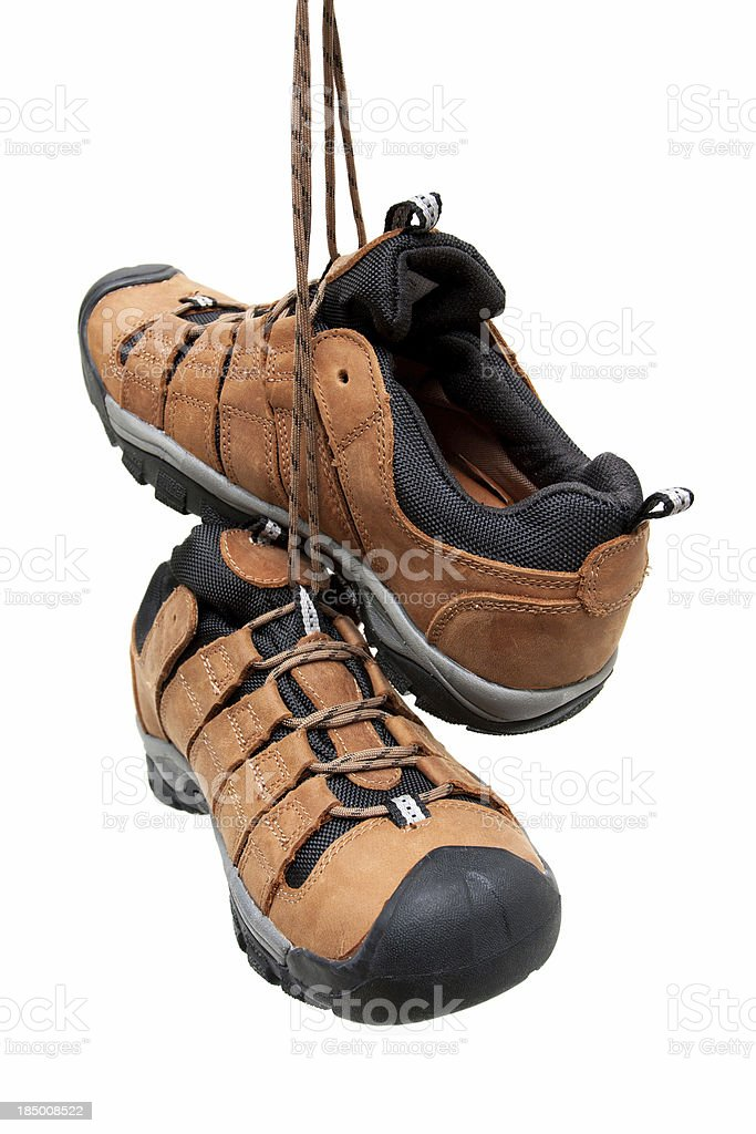 Hiking boots hanging isolated on white background stock photo