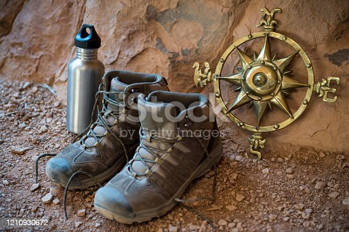 Well-used hiking boots sitting next to old fashioned compass rose outdoors in a red rock cave