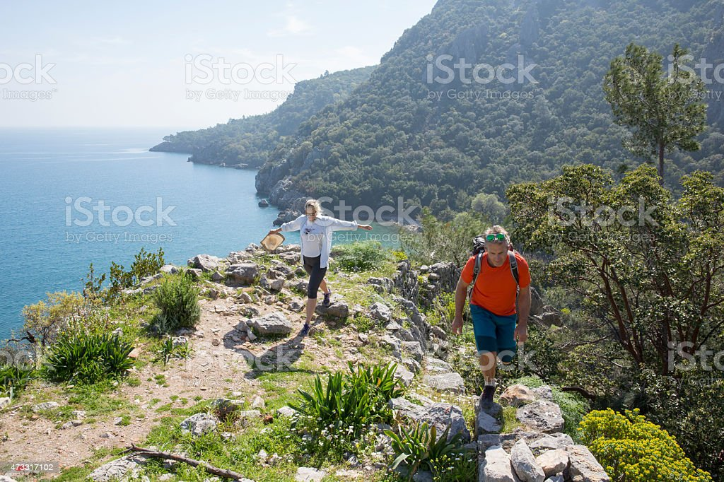 Hiking couple ascend mountain ridge crest above sea stock photo