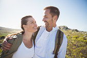 Hiking couple embracing and smiling on country terrain on a sunny day