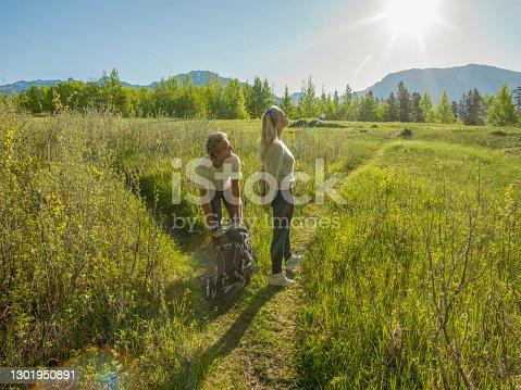 istock Hiking couple follow path through green mountain meadow 1301950891