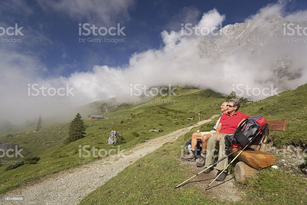 hiking couple on bench in alp landscape royalty-free stock photo