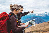hiking couple with map in mountain.
