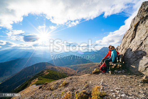 sporty fit extreme hiking mountaineers couple woman man in their fourties taking a short rest on bench high up in moiuntains on sunny autumn day starshapped sun enjoying beautiful outlook