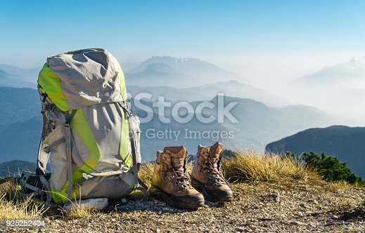 istock Hiking equipment. Backpack and boots on top of mountain. 925252404