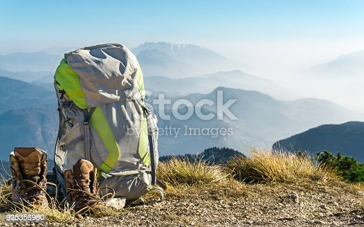 istock Hiking equipment. Backpack and boots on top of mountain. 925356980