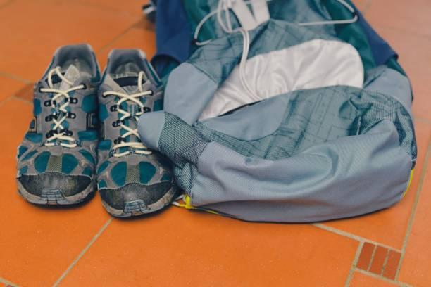 Hiking equipment: backpack and trekking boots on the floor. Horizontal photo and brown background. Tourist backgrounds and still-life. Preparation and planning for the travelling. Concept of the active lifestyle. stock photo